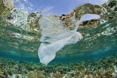 Sachet en plastique dans l'océan sur le récif coralien Photos stock