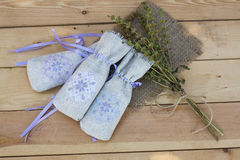Sachet with ukrainian embroidery, sheaf of wheat and dried herbs on wooden background Stock Photo