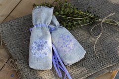 Sachet with ukrainian embroidery, sheaf of wheat and dried herbs on wooden background Stock Photos
