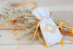 Sachet with ukrainian embroidery, wheat and oat on wooden background Royalty Free Stock Photo
