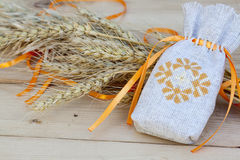 Sachet with ukrainian embroidery, wheat and oat on wooden background Stock Images