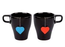 Sachets à thé avec les lables en forme de coeur dans des cuvettes Images stock