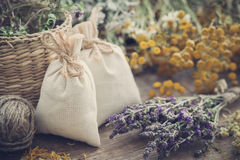Sachets filled with dried herbs and bunches of healing herbs. Royalty Free Stock Images