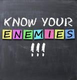 Sachez que vos ennemis textotent sur un tableau noir avec la craie et les autocollants Image stock