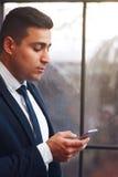 Sachlicher Mann, der Smartphone untersucht Lizenzfreies Stockfoto