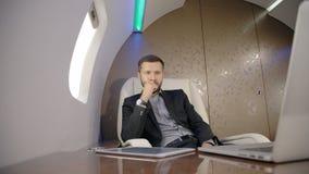 Sachverständiger Analytiker des jungen Geschäftsmanninvestors, der vor dem Laptop, denkend während des Fluges im Flugzeug sitzt stock video