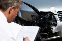 Sachverständiger, der das Auto mit einbezogen in Unfall kontrolliert Stockfoto