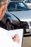 Sachverständiger, der das Auto mit einbezogen in Unfall kontrolliert Stockfotografie