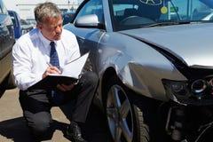 Sachverständiger, der das Auto mit einbezogen in Unfall kontrolliert Stockbild