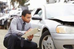 Sachverständiger, der das Auto mit einbezogen in Unfall kontrolliert Lizenzfreie Stockfotos
