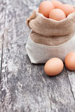 Sack bag with eggs on the old table Royalty Free Stock Image