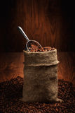 Sack of coffee beans and scoop. On a wooden backgroundund. Royalty Free Stock Photo
