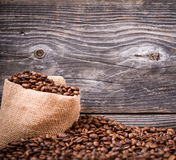 Sack of coffee beans on wood background Stock Photo