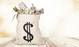 Sack with dollar sign filled with money on light Stock Photo