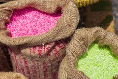 Sack of Dried tapioca pink and green on the wooden table royalty free stock images