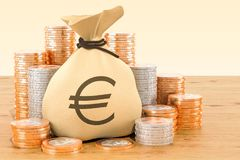 Sack with euro symbol and euro coins around on the wooden table. 3D Stock Photography