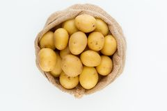 Sack of fresh raw potatoes on wooden background, top view.  Stock Photography