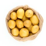 Sack of fresh raw potatoes on wooden background, top view. Sack of fresh raw potatoes on wooden background, top vie Royalty Free Stock Image