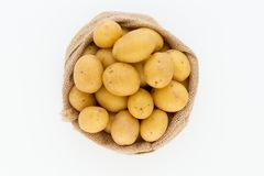 Sack of fresh raw potatoes on wooden background, top view.  Royalty Free Stock Photography