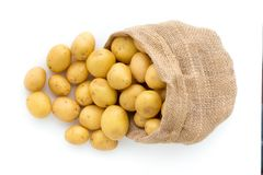 Sack of fresh raw potatoes on wooden background, top view.  Royalty Free Stock Photos