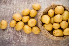 Sack of fresh raw potatoes on wooden background, top view. Sack of fresh raw potatoes on wooden background, top view Stock Image