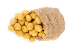 Sack of fresh raw potatoes on wooden background, top view.  Stock Images