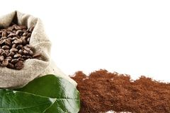 Sack full of coffee beans with green leaf backdrop. Bag full of coffee beans with green leaf, powder coffee at the bottom on white background Royalty Free Stock Photo