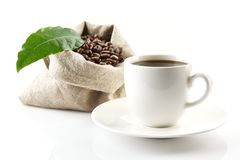 Sack full of coffee beans with green leaf and coffee cup Stock Image