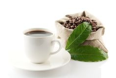 Sack full of coffee beans with green leaves and coffee cup Royalty Free Stock Photo