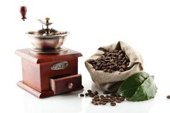 Sack full of coffee beans with green leaves with mill Royalty Free Stock Photos