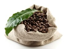 Sack full of coffee beans on white with green leaf Stock Photography