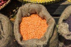 Sack getrocknete orange Bohnen-Linsen auf dem Holztisch Stockbild
