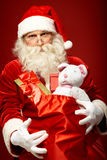 Sack of gifts. Portrait of generous Santa Claus holding presents in big red sack Royalty Free Stock Images