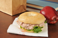 Sack lunch. A tunafish sandwich on a bagel with an apple and school books Stock Photos