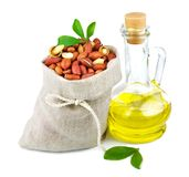 Sack of peanut and glass bottle of oil with leaves. Macro view of peanut in flax sack and glass bottle of oil with leaves isolated on white background Stock Photo