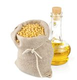 Sack of pine nuts and glass bottle of oil. Macro view of pine nuts in flax sack and glass bottle of oil isolated on white background Royalty Free Stock Photography