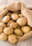 Sack Of Potatoes. Burlap sack of new potatoes on rustic table Royalty Free Stock Image