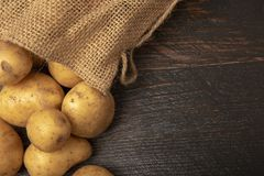 Sack of potatoes on wooden background. With copy space royalty free stock photos