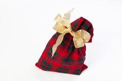 Sack present with golden ribbon. Checkered sack with golden ribbon for gift or present isolated over white Royalty Free Stock Image