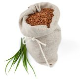 Sack of red rice with greens. Macro view of sack of red rice with greens isolated on white background Stock Images