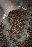 A sack of roasted arabica coffee beans. On a dark wooden background Stock Photos