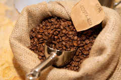 Sack of roasted coffee beans with metal scoop. Sacks of roasted flavoured coffee beans with metal scoop and paper label Royalty Free Stock Images