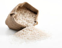 Sack with scattered rice on white background. Stock Photography