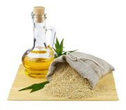 Sack of sesame seeds and glass bottle of oil. Macro view of sesame seeds in flax sack and glass bottle of sesame oil isolated on white background Royalty Free Stock Photos