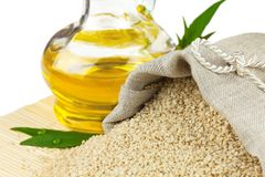 Sack of sesame seeds and glass bottle of oil Royalty Free Stock Photography