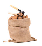 Sack with walnuts and nutcracker. Royalty Free Stock Photography