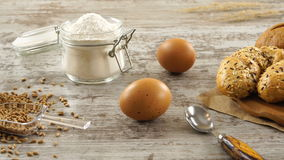 Sack of wheat, flour, garlic, eggs, and fresh bread on a rustic wooden table. stock footage