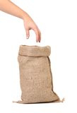 Sack with wheat flour and hand. Royalty Free Stock Photos