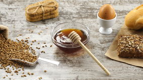Sack of wheat, honey, cookies, egg, and fresh bread on a rustic wooden table. Countryside breakfast. stock video