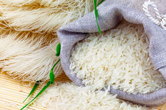 Sack of white rice and rice vermicelli. Macro view of sack with white rice and rice vermicelli with greens on the mat Stock Photos